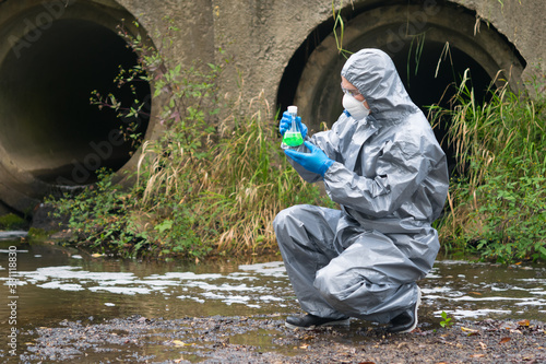 Vászonkép a laboratory specialist in protective clothing and a mask holds a flask with a g