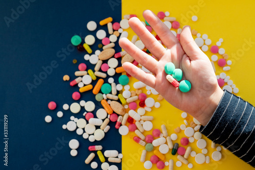 Top view of child hand holding tablet pills against colorful background Canvas Print