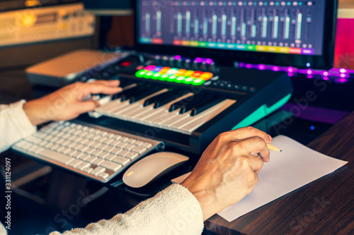 Cuadros en Lienzo male composer hands writing lyric on paper and creating melody on midi keyboard