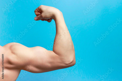 Male arm with large muscles close-up, rear view, blue background Canvas Print