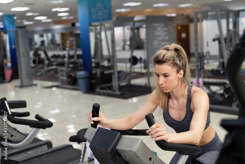 obraz PCV Young woman on bike at gym exercising
