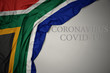 canvas print picture - waving national flag of south africa on a gray background with text coronavirus covid-19 . concept.