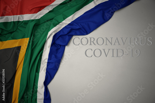 Fototapeta waving national flag of south africa on a gray background with text coronavirus covid-19