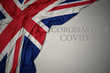 canvas print picture waving national flag of great britain on a gray background with text coronavirus covid-19 . concept.
