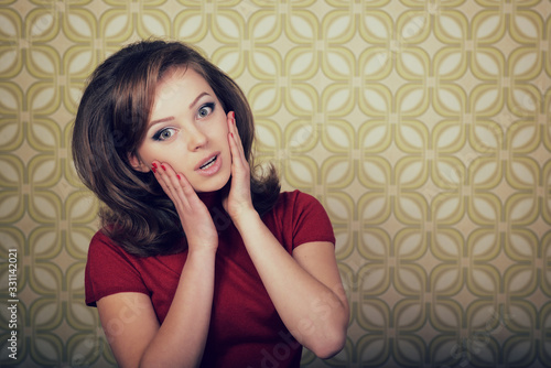 Photo Young smiling ecstatic woman looking at camera in room with vintage wallpaper, retro stylization 60-70s