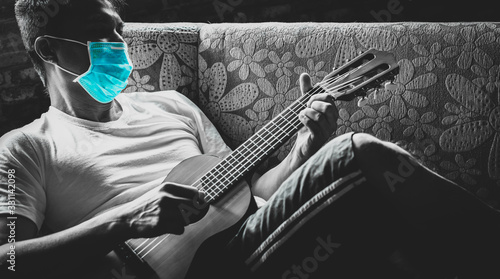 Fotomural asian man at risk of infection in coronavirus covid 19 playing guitar for relaxa
