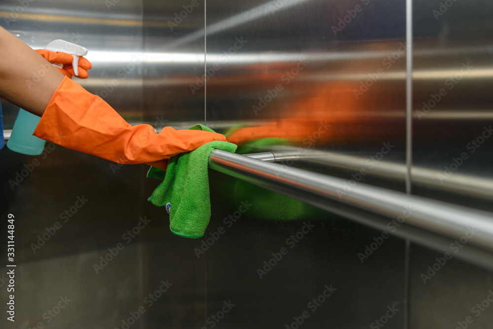 Fototapeta Woman hand in protective orange rubber gloves holding green microfiber cleaning cloth and wiping dust using a spray sterilizing solution make cleaning and disinfection for good hygiene
