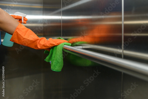 Obraz Woman hand in protective orange rubber gloves holding green microfiber cleaning cloth and wiping dust using a spray sterilizing solution make cleaning and disinfection for good hygiene - fototapety do salonu
