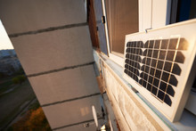 Solar Panel On The Window Of A High-rise Residential Building Against A Background Of A Sleeping Area Of The City At Sunset. Converting Solar Radiation Into Electricity