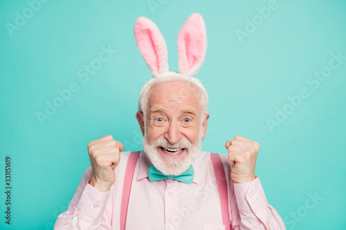 Close up photo of funky excited positive retired gentleman celebrate traditional easter event raise fists enjoy victory wear pink rabbit headband isolated over turquoise color background
