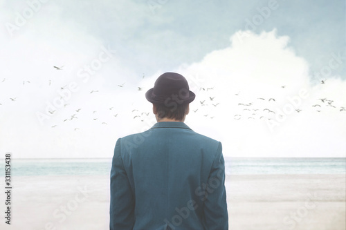 Obraz man in blue suite and bowler observing seagulls over the sea, surreal abstract concept - fototapety do salonu