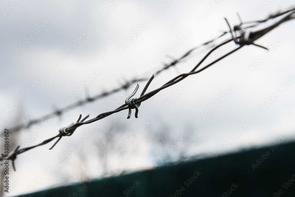 Fototapeta Barbed wire against cloudy sky. Near the prison or restricted area. Blurred concept photo. Closeup.