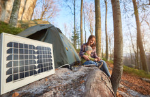 Close-up Of A Tourist Solar Panel In A Campsite On A Sunny Autumn Day Against The Background Of A Young Family. Mother And Baby Watching Something At A Mobile Phone While Enjoying Outdoor Activities