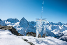 Background Of Pouring Blue Mineral Water In Transparent Glass Over Winter Landscape Of Mountains Higher Than Clouds