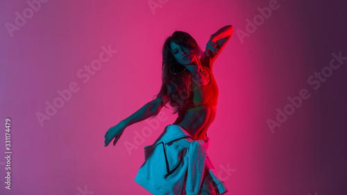 Sexy pretty young woman dancer in stylish youth clothes dancing and posing in a room with bright neon blue-pink color. Sports girl enjoys a dance in the studio with multi-colored ultraviolet light.