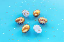 Painted Gold And White Eggs On A Blue Background With Confetti. Easter Concept. Top View