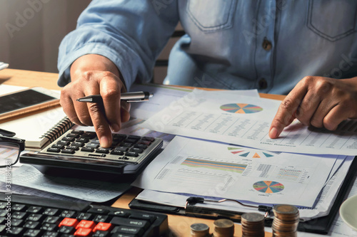 Fototapeta accounting concept. businesswoman working using calculator with money stack in office obraz