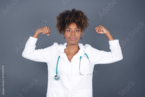 Fotografiet Waist up shot of caucasian doctor woman raises arms to show her muscles feels confident in victory, looks strong and independent, smiles positively at camera, stands against gray background