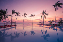 Luxury Sunset Over Infinity Pool In A Summer Beachfront Hotel Resort At Tropical Landscape. Tranquil Beach Holiday Vacation Background Mood. Amazing Island Sunset Beach View, Palms Swimming Pool