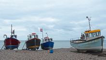 Part Of The Local Fishing Fleet Stranded On The Pebble Beach At Beer In South Devon, UK. Vessels Are Towed To And From The Sea By Tractor
