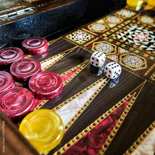 Photo Closeup of a colorful Backgammon with dice on it on the table under the lights