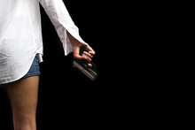 Asian Woman Portrait (low Key) Who Wear White Shirt Is Holding A Gun And Put The Gun Beside The Body Isolated On Black Background. Teenager Problems And Crime Concept.