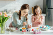 selective focus of cute child and mother painting easter eggs near tulips
