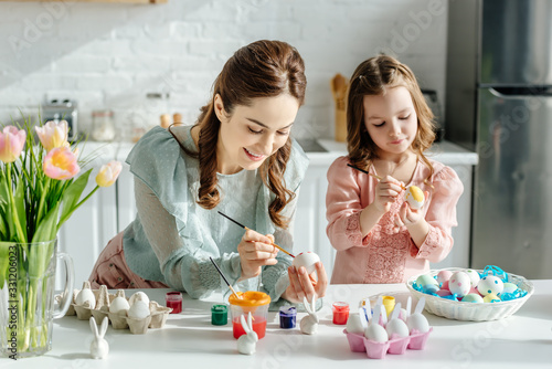 selective focus of cute child and mother painting easter eggs near tulips #331206023