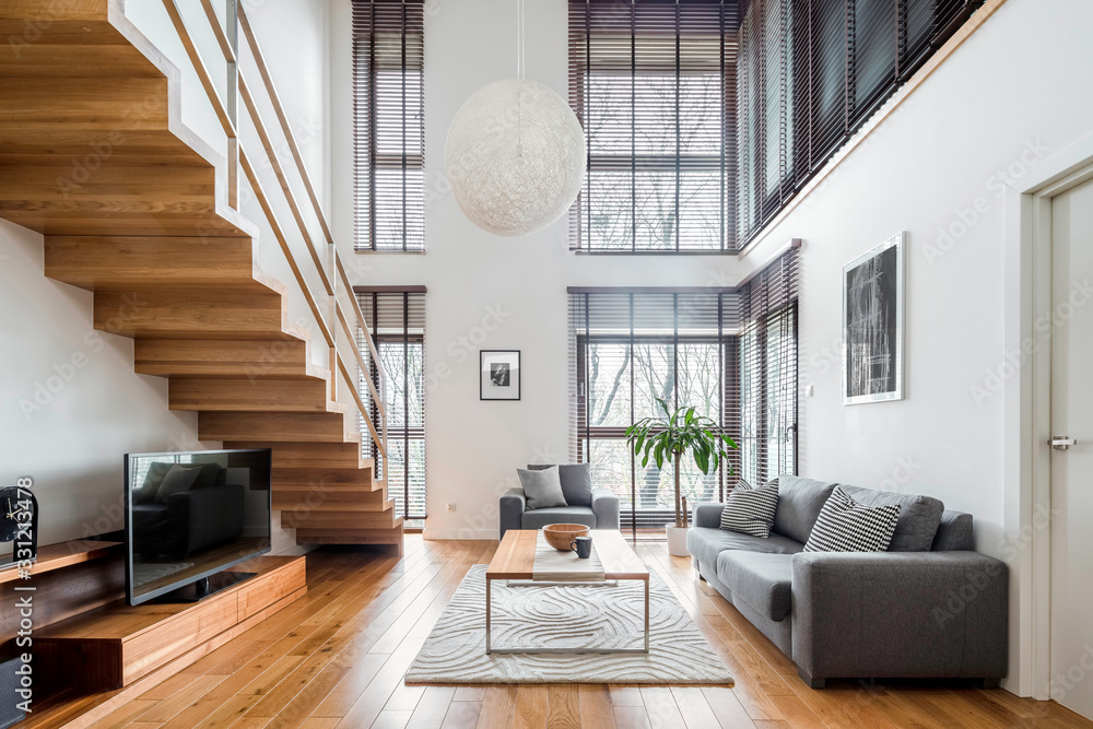 Fototapeta Spacious living room with wooden stairs