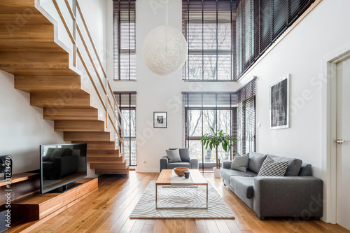 Obraz Spacious living room with wooden stairs - fototapety do salonu