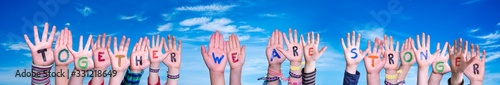 Children Hands Building Colorful Word Together We Are Stronger. Blue Sky As Background