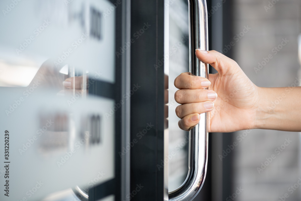 Fototapeta Closeup woman hand holding the door bar to open the door with glass reflection background.
