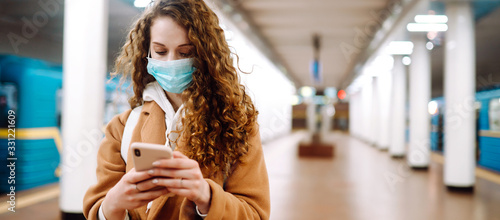 Obraz Long edge. Girl in protective sterile medical mask watching news on the phone about coronavirus in subway tunnel. The concept of preventing the spread of the epidemic. - fototapety do salonu