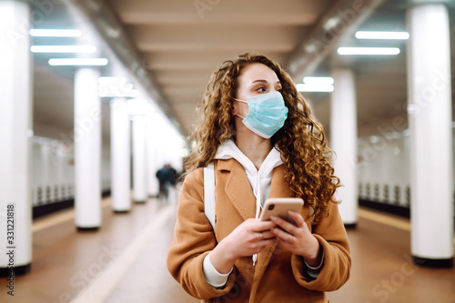 Photo Girl in protective sterile medical mask with a phone  at subway station