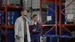 Slow motion tracking shot of middle aged engineer in white coat giving instructions to young material handler making notes while walking in industrial storage