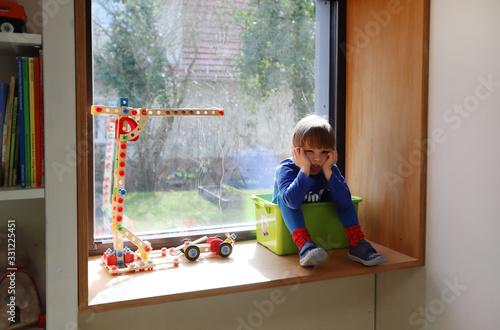 Ein vierjähriger Junge sitzt gelangweilt in seinem Zimmer am 18.03.2020. #331225451