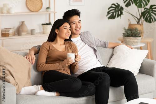 Obraz Filipino couple resting at home and watching tv - fototapety do salonu