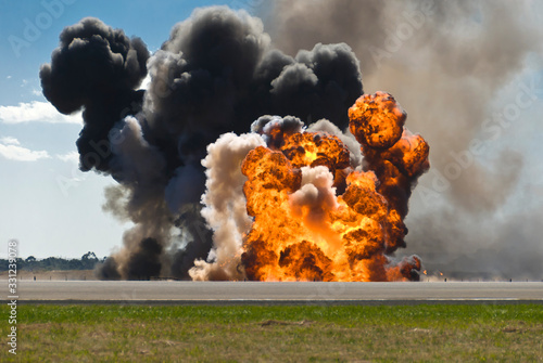 Fotografie, Tablou Firey explosion with thick black smoke on an airport runway.