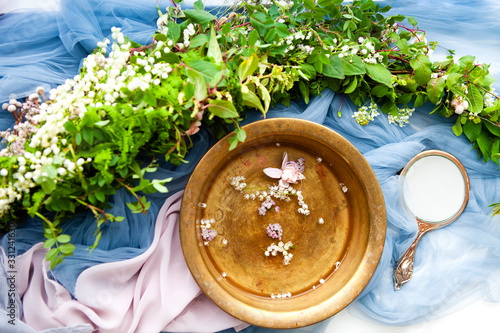 Fancy hand mirror and bowl of water among leaves and flowers prepared for skin c Canvas Print
