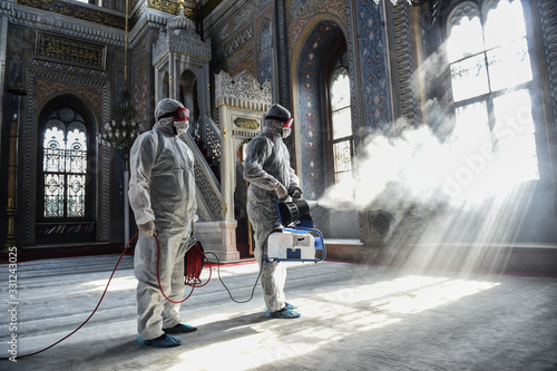 Obraz A member of Istanbul's Municipality disinfects the mosque in Istanbul to prevent the spread of the COVID-19, the novel coronavirus - fototapety do salonu