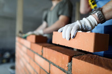 Two Workers Making Red Brick Wall At Construction Site