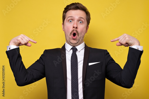 Photographie Positive young man with mustache smiling and pointing at himself with index fingers