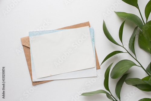Fototapeta mockup card with plants. invitation card with environment and details Mockup with postcard and flowers on white background. obraz
