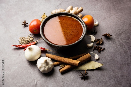 North Indian basic spicy Curry or masala for vegetables or chicken or mutton recipe shown with ingredients, served in a bowl. selective focus	homemade, restaurant, hot, oil, dark, red, indian, india,