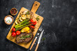 canvas print picture Beef steak grilled with vegetables on black stone table.