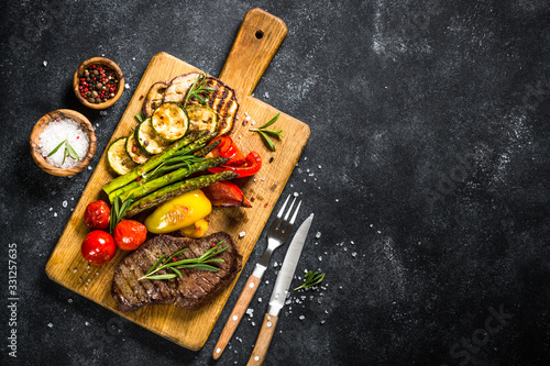 Beef steak grilled with vegetables on black stone table. Canvas Print