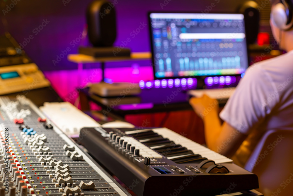 Fototapeta back of male asian professional producer working in recording studio, focus on mixing console fader. music production concept