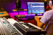 canvas print picture - back of male asian professional producer working in recording studio, focus on mixing console fader. music production concept