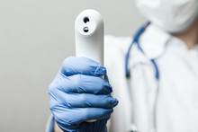 Doctor Pointing Infrared Thermometer Gun To Check Body Temperature Epidemic Virus Outbreak Concept