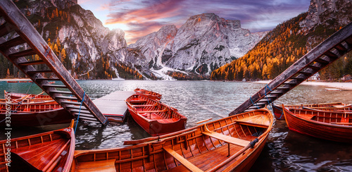 Wall mural - Spectacular famous place with typical wooden boats on the alpine lake Braies in Dolomites. Impressive Lago di Braies during sunset. Amazing Autumn nature landscape. Iconic location for photographers